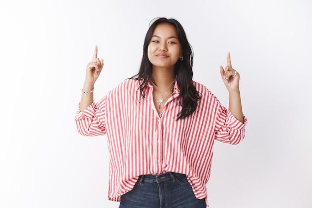 Meisje toont trots haar tentoonstelling naar boven gericht. portret van een knappe, tevreden, schattige vietnamese vrouw in een gestreepte roze blouse die glimlacht en het hoofd opheft, wat aangeeft dat de promo naar boven zou kunnen