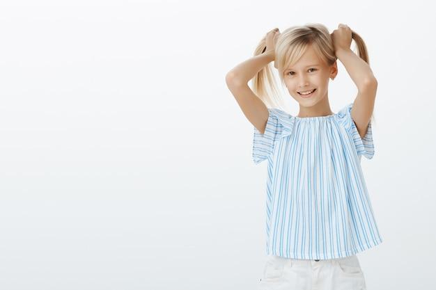Meisje toont vrienden haar nieuwe oorbellen. blij tevreden meisje met blond haar, dat haar opheft en vreugdevol glimlacht