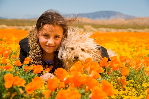Meisje tot in papaver veld met hond