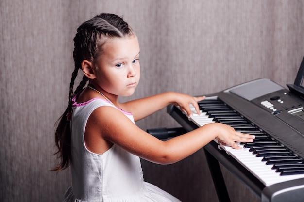Meisje traint akkoorden op een elektronische synthesizer in een interieur
