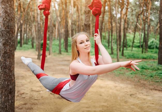 Meisje traint in een hangmat voor aero yoga.