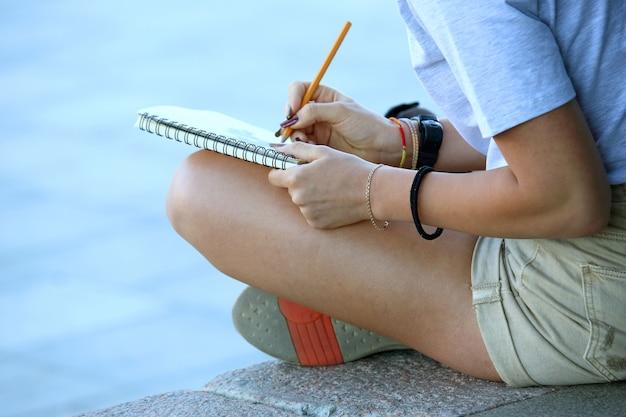 Meisje trekt in een notitieboekje zittend op de stoep