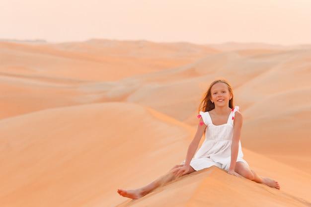 Meisje tussen de duinen in de rub al-khali-woestijn in de verenigde arabische emiraten