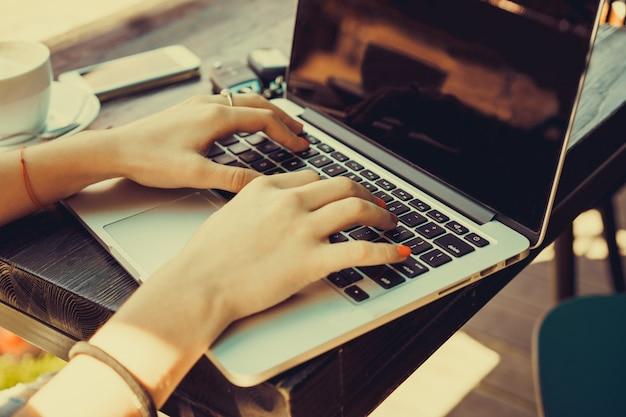 Meisje typen op een laptop met een kopje koffie ernaast