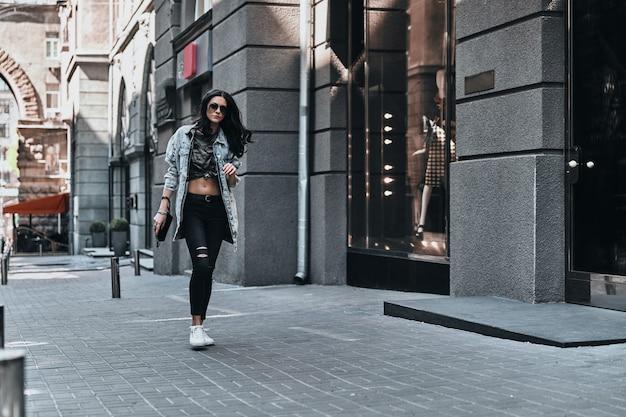 Meisje uit de stad. volledige lengte van jonge aantrekkelijke vrouw in spijkerjasje wandelen