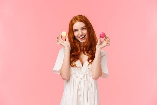 Meisje uitnodigend zitten met haar genieten van thee met desserts. verbluffende, verleidelijke roodharige vrouw in witte jurk, die twee macarons laat zien die verleidelijke vriend hebben bijten, opgewonden glimlachend, staande roze achtergrond
