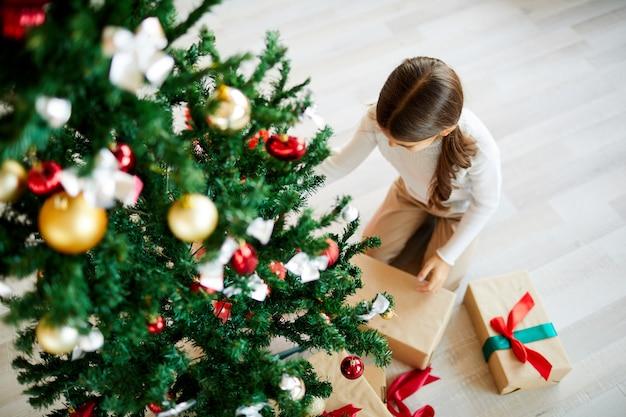 Meisje uitpakken kerstcadeau, bovenaanzicht