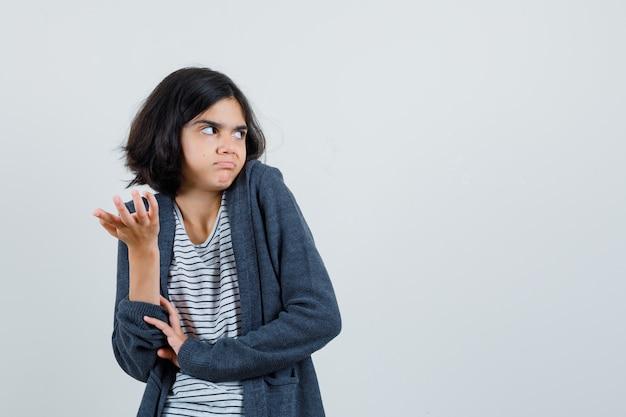 Meisje uitrekken hand in verbaasd gebaar door schouderophalend in t-shirt