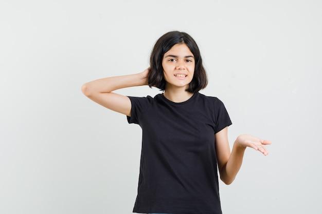 Meisje uitrekkende hand op vragende manier in zwart t-shirt en op zoek vrolijk, vooraanzicht.