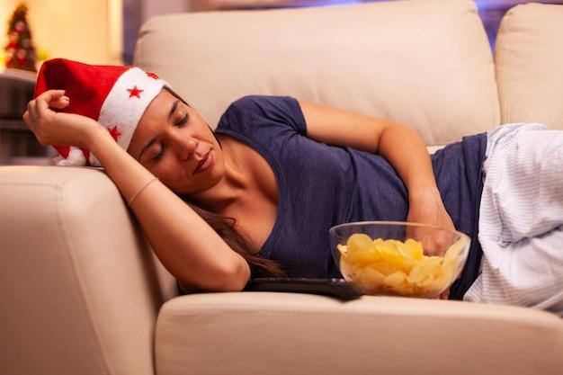 Meisje valt in slaap op de bank in de met kerst versierde keuken