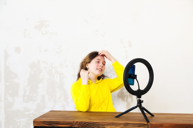 Meisje van 16 jaar oud video opnemen op smartphone en zichzelf met ringlamp aansteken aan tafel in lichte kamer