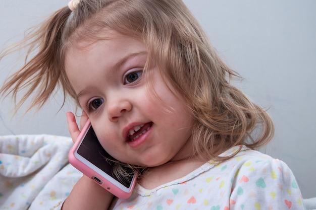 Meisje van 2 jaar oud met een telefoon in haar hand - thuis spelen tijdens het praten aan de telefoon