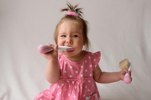 Meisje van 6 maanden oud met een kam in de hand op een witte ondergrond