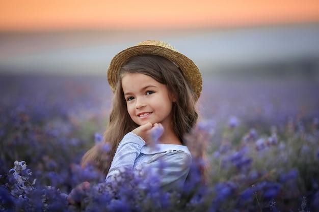 Meisje van 8 jaar gekleed in paarse katoenen jurk verzamelt lavendelbloemen in natuurlijk veld