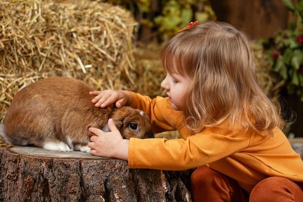 Meisje van de baby aaien konijn