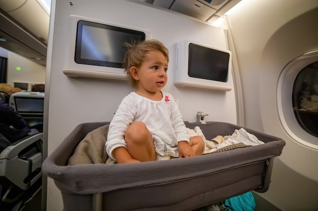 Meisje van de baby wakker afret slapen in bassinet on airplane. baby passagier aan boord