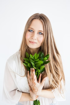 Meisje van de europese uitstraling in lichte kleding met groene takken.