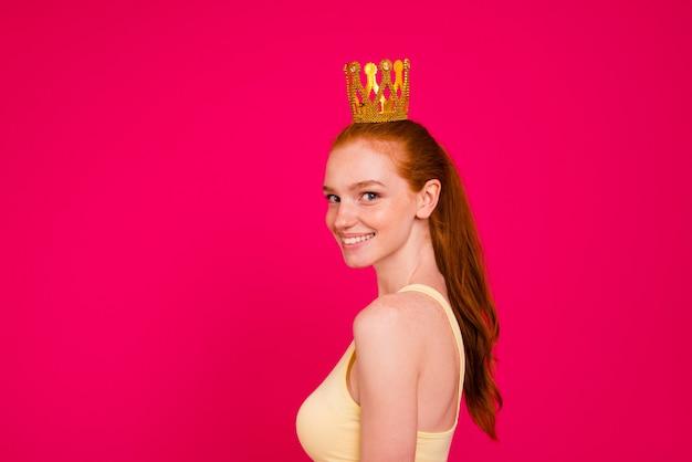 Meisje van de portret het mooie roodharige dat over roze muur wordt geïsoleerd