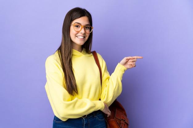 Meisje van de tiener het braziliaanse student over geïsoleerde purpere muur die vinger aan de kant richten