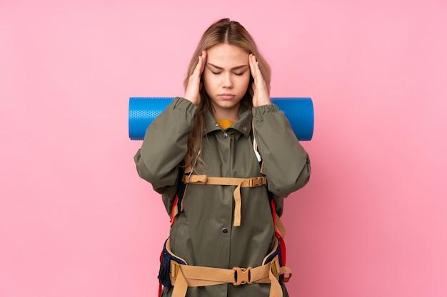 Meisje van de tiener het russische bergbeklimmer met een grote rugzak die op roze wordt geïsoleerd
