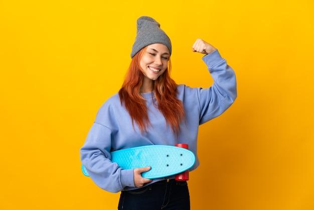 Meisje van de tiener het russische die skater op gele muur wordt geïsoleerd die sterk gebaar doet