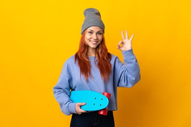 Meisje van de tiener het russische schaatser dat op gele muur wordt geïsoleerd die ok teken met vingers toont