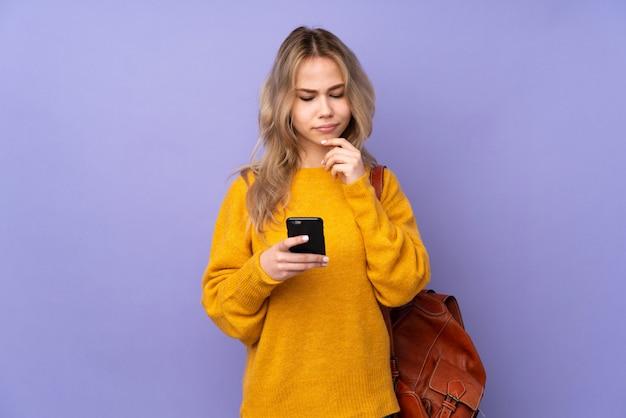 Meisje van de tiener het russische student op purpere muur die en een bericht denken verzenden