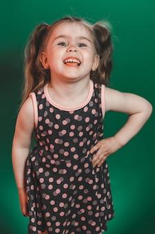 Meisje van drie jaar met staarten in jurk poseren in studio op groene achtergrond 2021