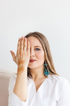 Meisje van europese uitstraling, henna puttend uit handen, mahendi, meisje in lichte kleding, yoga, spirituele ontwikkeling