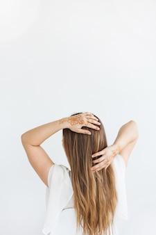 Meisje van europese uitstraling, henna puttend uit handen, mahendi, meisje in lichte kleren