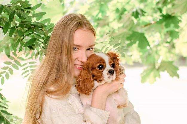 Meisje van het portret het gelukkige blonde met lang haar die leuke rasechte puppy cavalier king charles spaniel houden.
