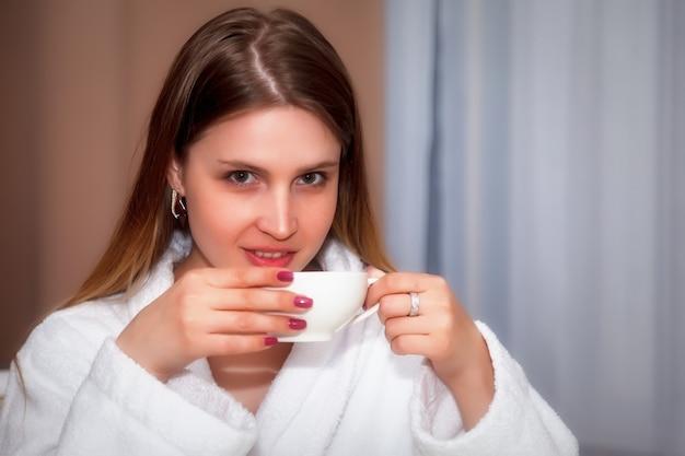 Meisje van slavische verschijning in jas met witte kop zit aan tafel. vrouw neemt de emoties van de acteur. jonge charmante vrouw zit in hotelkamer en drinkt koffie of thee. ontspan concept