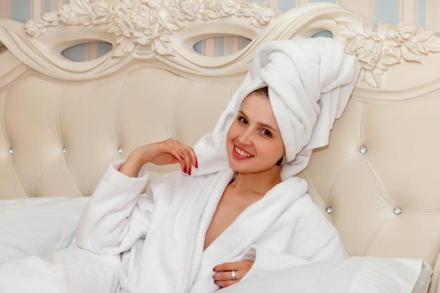 Meisje van slavische verschijning in wit gewaad op bed
