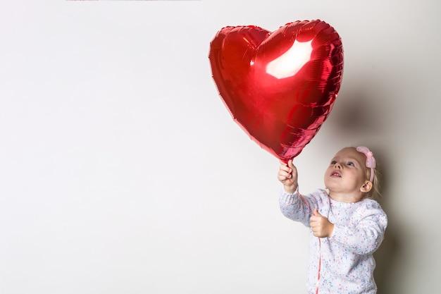 Meisje vangt een hart-luchtballon op een lichte achtergrond. concept voor valentijnsdag, verjaardag. banner.