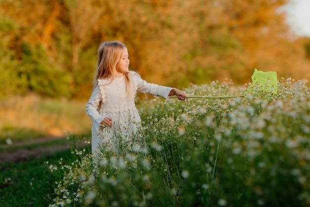 Meisje vangt vlinders netto moer veld madeliefjes in de zomer bij zonsondergang