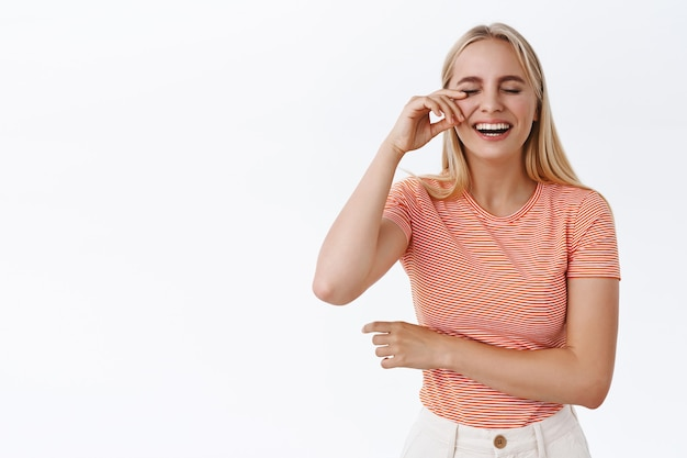 Meisje veegt traan weg van het lachen zo hard, genietend van hilarische komedie. zorgeloze gelukkige blonde vrouw in gestreept t-shirt met plezier, giechelen, stand-up bijwonen, staande witte achtergrond vrolijk