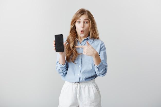 Meisje verbaasd over nieuwe telefoon. portret van gefascineerde geschokte jonge europese vrouw met blond haar in blouse met smartphone, wijzend op apparaat, zegt wow, verbazing uitend