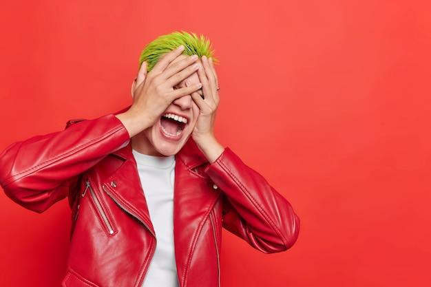 Meisje verbergt gezicht met handen roept luid houdt mond wijd open draagt leren jas op rode lege kopie ruimte voor uw advertentie