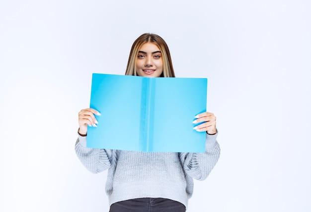 Meisje verbergt haar gezicht achter een blauwe map.