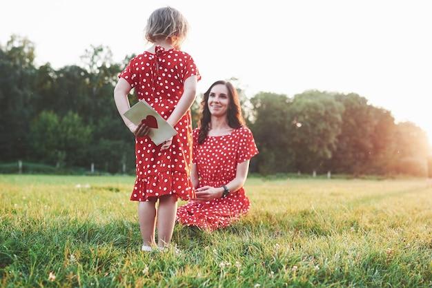 Meisje verbergt het boek met rood hart op de rug van de lachende zittende moeder