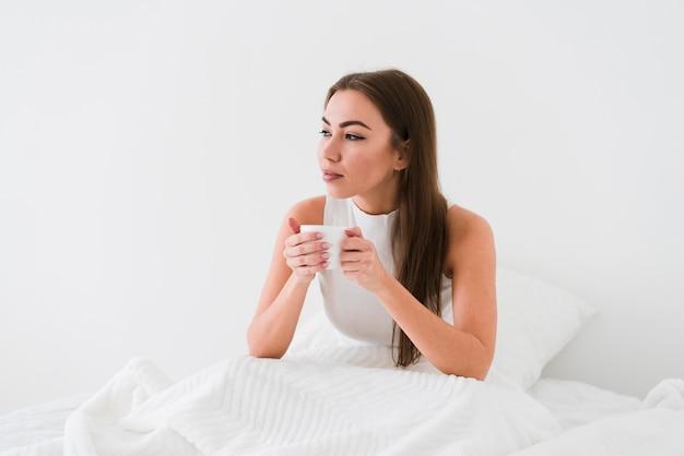 Meisje verblijft in bed en drinkt koffie