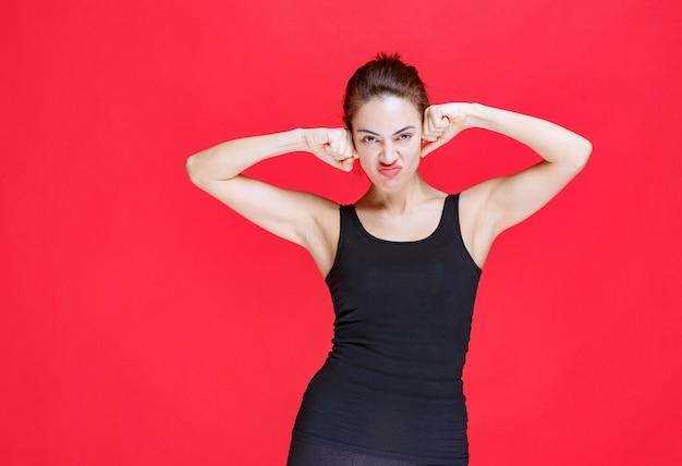 Meisje verenigt haar vuisten op haar hoofd en ziet er agressief uit. hoge kwaliteit foto