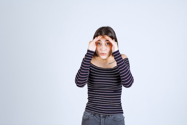 Meisje verenigt handen op haar voorhoofd en kijkt ernaar uit.