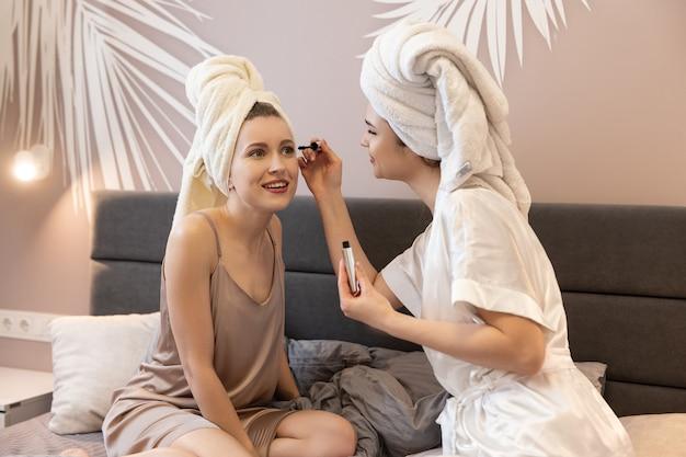 Meisje verf wimpers aan haar vriendin. jonge lachende europese vrouwen met ingepakte badhanddoeken op hoofden die op bed liggen. concept van meisjesfeest thuis. interieur van slaapkamer in modern appartement