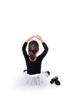 Meisje verkleed als balletdanseres zit op de vloer en heft haar armen op