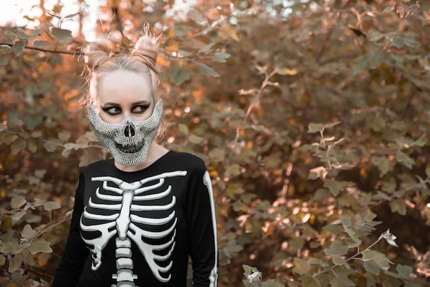 Meisje verkleed als een skelet in het herfstbos. portret. detailopname. halloween