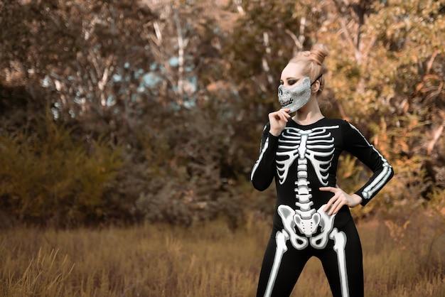 Meisje verkleed als een skelet in het herfstbos. ze stond vreselijk naar de camera te staren. halloween