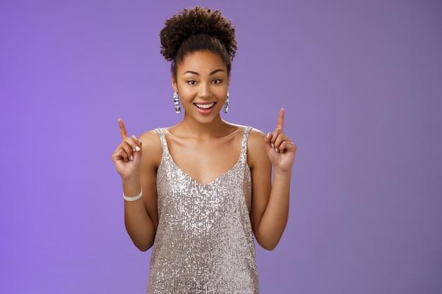 Meisje verkleedbal wachten vriendje pick-up limousine. elegante afro-amerikaanse jonge vrouw glinsterende glanzende luxe jurk oorbellen die naar boven wijzen wijsvingers voelen zich gelukkig opgewonden feest de hele nacht.