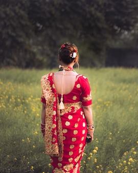 Meisje verkleedt zich in sari voor huwelijksceremonie die op het mosterdveld staat