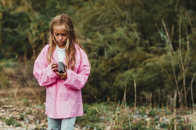 Meisje verloor in het bos op een regenachtige dag en probeerde via gps met haar gps-telefoon te communiceren